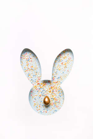 Creative layout made of Hole Easter Bunny face and colored sugar sprinkles with golden egg nose. Stockfoto