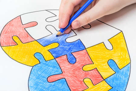 World Autism Awareness day. Childrens hand draws heart from multi-colored puzzles. Mental health care concept. Stock fotó
