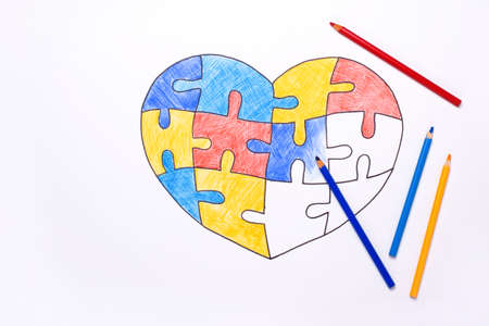 World Autism Awareness day. Color pencils and unfinished drawing heart from multi-colored puzzles. Mental health care concept.