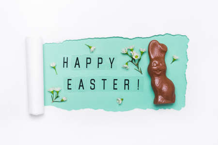 Creative layout made of torn hole, Happy Easter text and Chocolate bunny.