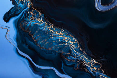 Acrylic Fluid Art. Golden wave of particles and and blue overflows. Abstract stone background or texture.