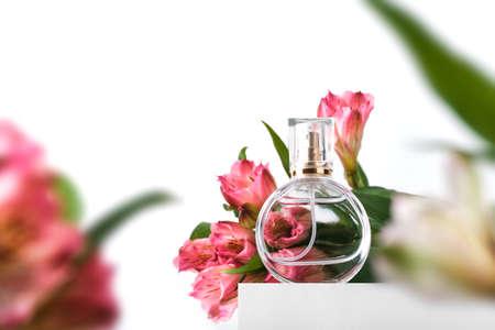 Glass perfume bottle on white podium. Floral arrangement. Minimal mockup style, soft focus, low angle