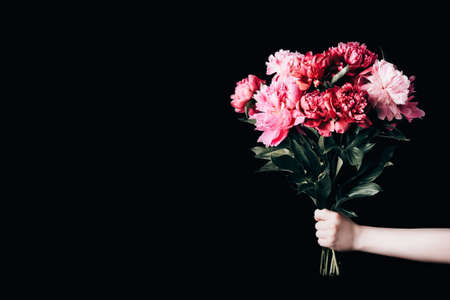 Female hand holds beautiful bouquet of peonies. Flower delivery concept