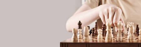 Banner with Faceless boy develops game strategy. Hand holds chess piece and makes a move, selective focus on hand