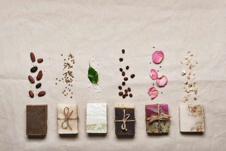 Natural soap bars with ingredients on linen cloth background. Diy cosmetics products