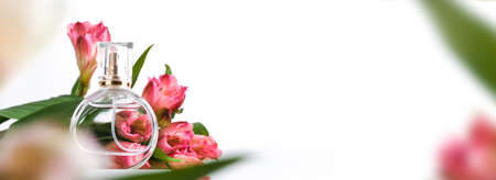 Banner with Glass perfume bottle on white podium. Floral arrangement. Minimal mockup style, soft focus, low angle