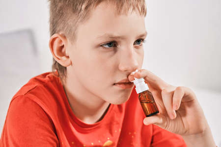 Blond Boy drips nose drops from runny nose. Treatment of colds and allergic rhinitis. Selective focus