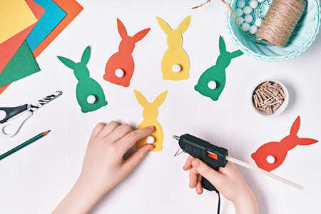 DIY Easter home decor from natural materials. Hands make garland of colored paper, twine and pom-poms