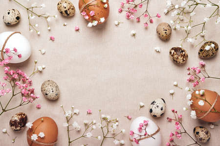 Easter eggs with natural flowers decor on linen background. Zero Waste Easter Concept. Frame for text in neutral colors Stock Photo
