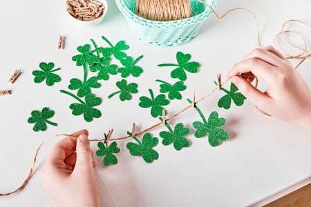 DIY St.Patricks Day decor. Hands make shamrocks garland of glitter paper on white table Stock Photo