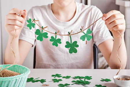 DIY St.Patricks Day decor. Happy boy make garland of shiny green paper. Selective focus Stock Photo - 164815600