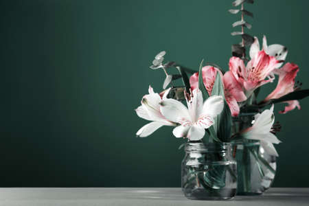Bouquet of beautiful flowers in glass bottles on green wall table background. Minimal Floral Festive Decoration, surreal tinted