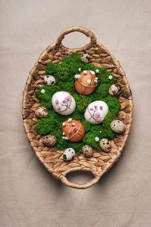 Easter eggs with natural flowers decor on linen tablecloth. Zero Waste Easter. Wicker basket with moss and decorated with twine and flowers eggs Stock Photo