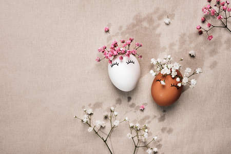 White and black Easter eggs with natural flowers decor. Zero Waste Easter Concept. Racial Equality symbol. Sunlight and floral shadows
