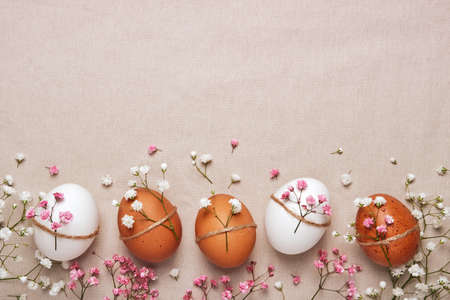 Easter eggs with natural flowers decor on linen background. Zero Waste Easter Concept in neutral colors Stock Photo