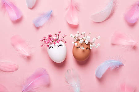White and black Easter eggs with natural flowers wreath on soft pink feathers background. Zero Waste Easter Concept. Racial Equality symbol