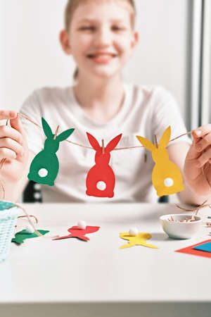 DIY Easter home decor from natural materials. Happy boy make garland of colored paper, twine and pom-poms. Selective focus
