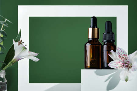 Natural skin care products concept. Herbal mineral cosmetics, serum, hyaluronic acid on white podium. Transparent dark glass bottle with dropper. Frame, shadows and copy space