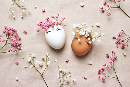 White and black Easter eggs with natural flowers wreath on linen background. Zero Waste Easter Concept. Racial Equality symbol Stock Photo