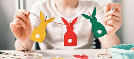 Banner with DIY Easter home decor. Happy boy make garland of colored paper, twine and pom-poms. Selective focus Stock Photo