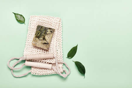 Eco friendly natural hygiene concept. Diy herbal soap and sisal washcloth on green background, copy space