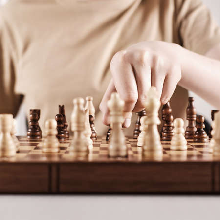 Faceless boy develops game strategy. Hand holds chess piece and makes a move, selective focus on hand Stock Photo