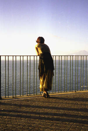 Woman of Sorrento on the terrace at sunset, with Mount Vesuvius and Naples in the background