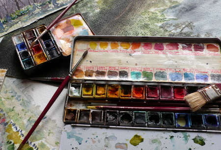 Work table with a passion for watercolor painting, with colors and brushes photo