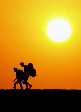 Two hikers, backpackers, a sunset in the background, with the big sun, Due escursionisti, zaino in spalla, sullo sfondo un tramonto , con il sole grande photo