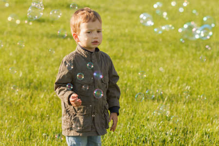 A little redhead boy blowing soap bubbles in summer park. Background of grass outdoor.