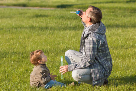 Happy dad and son playing together in the nature with soap bubbles