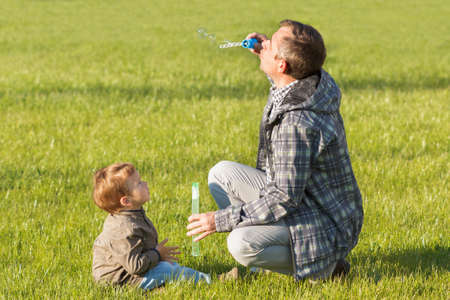 Father and son playing in the park with soap bubbles at the day time. Concept of parenting and family. Background of grass.