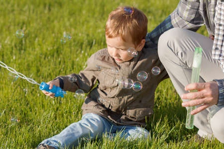Happy dad and his son playing together in the nature with soap bubbles Zdjęcie Seryjne