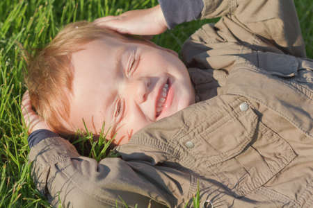 Happy, smiling boy laying on a grass in a park