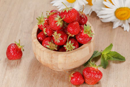 Fresh strawberries in a wooden bowl