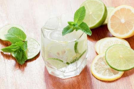 Un vaso de agua fría con limón y lima, cubitos de hielo y hojas de menta sobre una mesa de madera