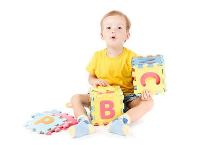Child playing and learning letters with colorful puzzles