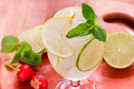 A glass of water with lemon lime strawberry and mint served with ice cubes on a wooden board.