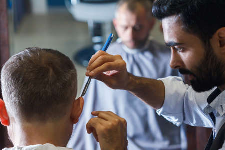 Male client getting haircut by hairdresser. Barbershop hair cutting. Zdjęcie Seryjne
