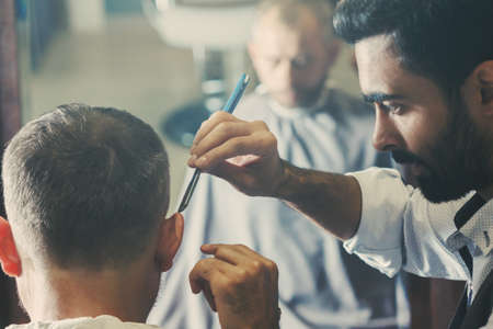 Barbershop hair cutting. Male client getting haircut by hairdresser Zdjęcie Seryjne