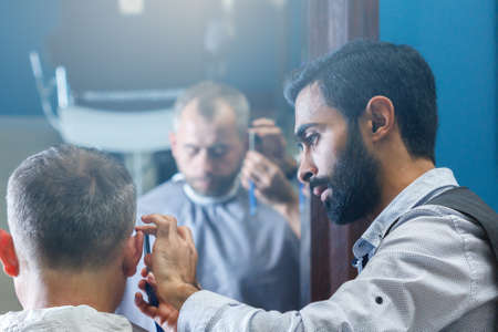 Male client getting haircut by hairdresser Zdjęcie Seryjne