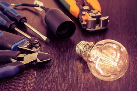 テーブルの上が燃える電球とソケットと他の電気技師用具です。