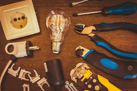 burning light bulb and socket and other electrician tools are on the table Фото со стока - 74296530