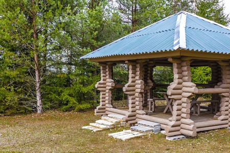 attic: gazebo made of logs on the edge of the forest for recreation and picnic