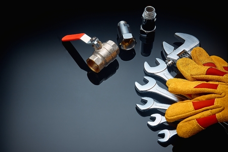 Plumbing accessories and tools on a dark background photographed close-up