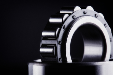 Close-up of a set of ball and roller bearings for repair lying on the desktop in the dark. Can be used as a background Standard-Bild