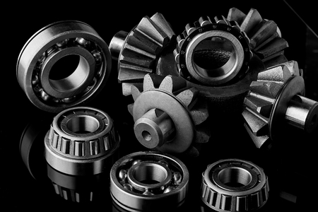 Gears, bearings and differential are on the table in the dark. Can be used as a background.