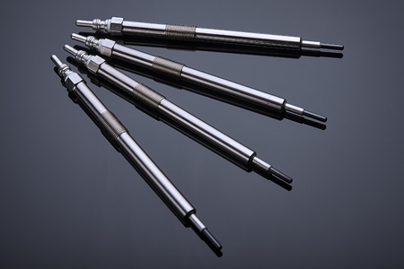 Four glow plugs for the diesel engine lie on a dark background, prepared for the next service Stockfoto