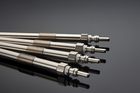 Four glow plugs for the diesel engine lie on a dark background, prepared for the next service Фото со стока