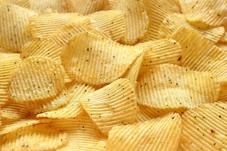 Textured gold background from natural corrugated potato chips with onion and sour cream